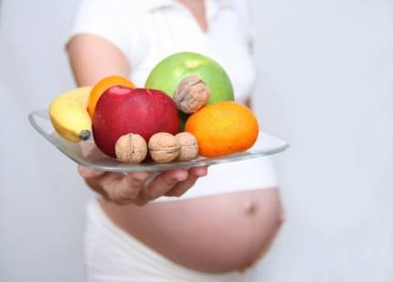 Donna incinta che mostra alimenti sani