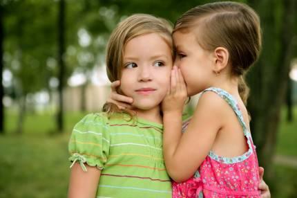 Una bambina sussurra nell'orecchio di un'altra