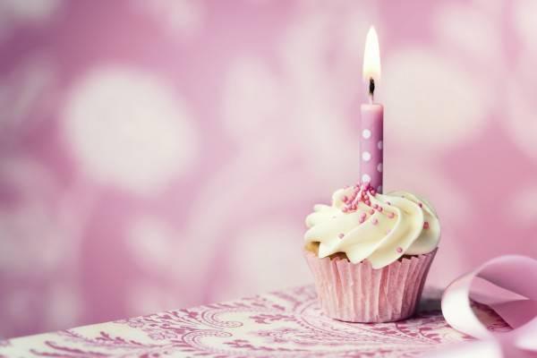 Candelina rosa su torta di compleanno