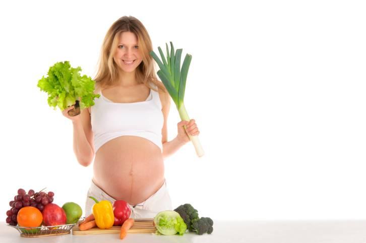 Donna incinta con frutta e verdura