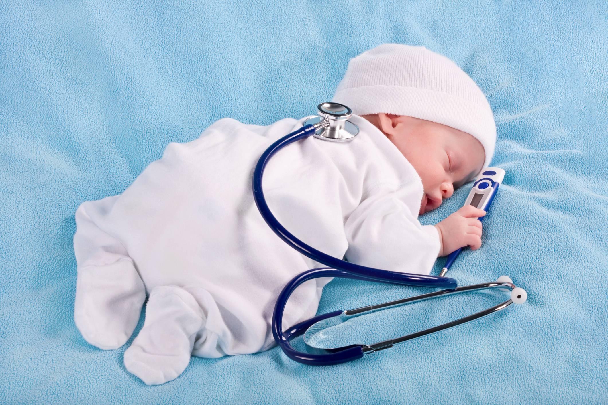 Neonato su letto con stetoscopio e termometro