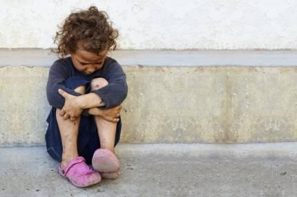 Bambina povera appoggiata su un muro