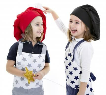 Due sorelle gemelle giocano con cappelli da chef