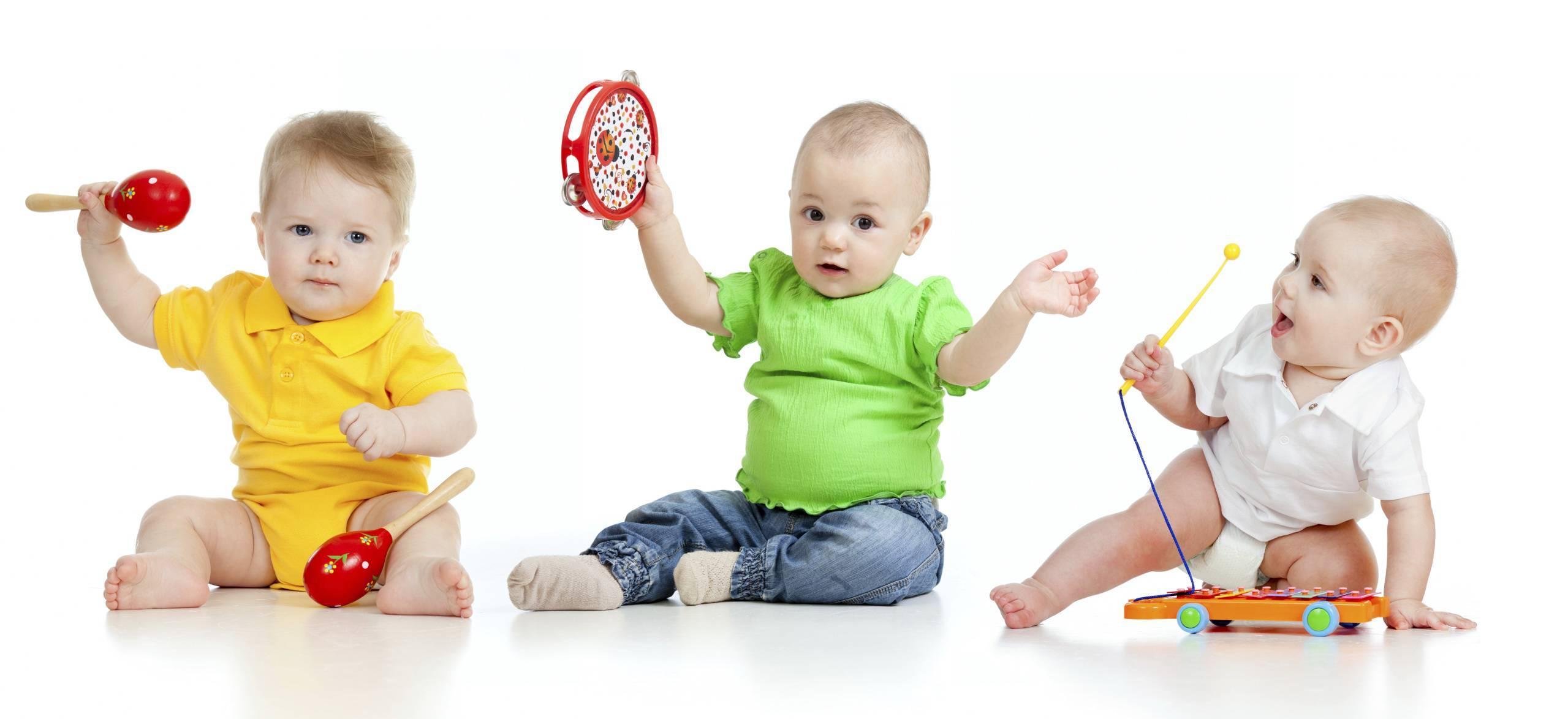 tre bambini si divertono a suonare con piccoli strumenti