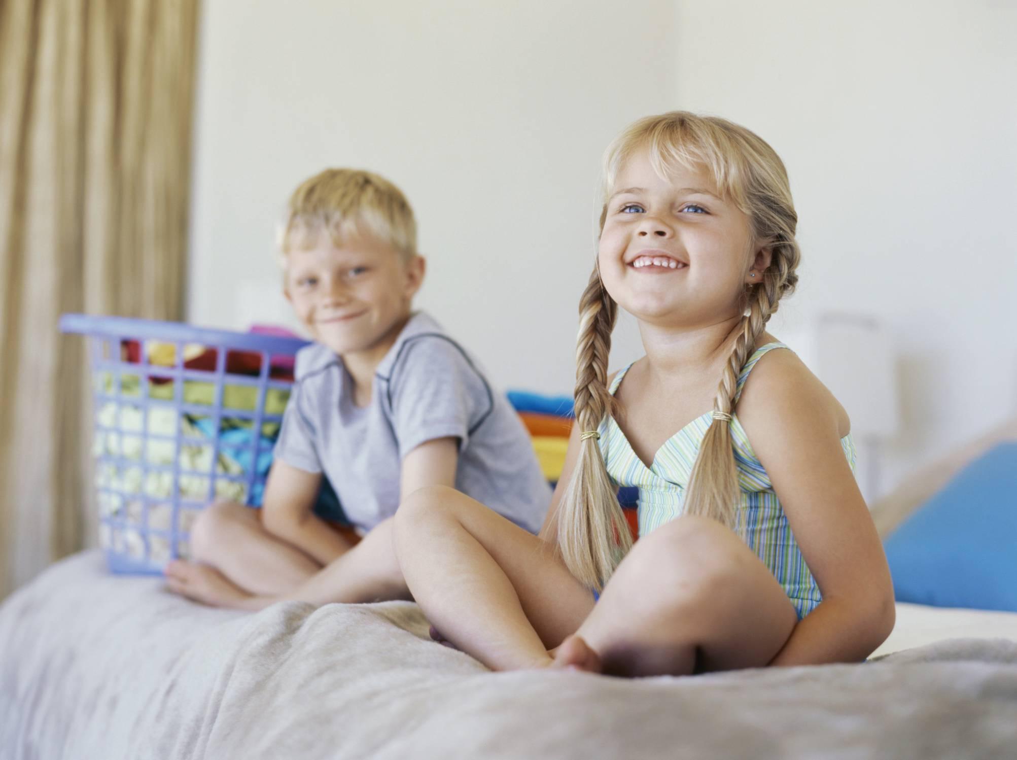 Fratello e sorella seduti sullo stesso letto
