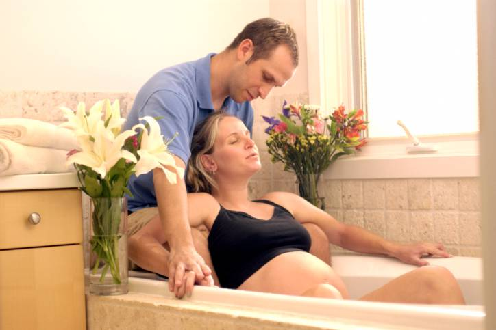 Donna in travaglio nella vasca supportata dal compagno