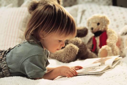 Bambina che sfoglia un libro illustrato