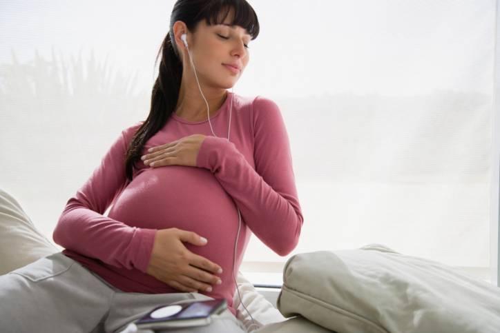 Donna incinta mentre ascolta musica da un lettore MP3