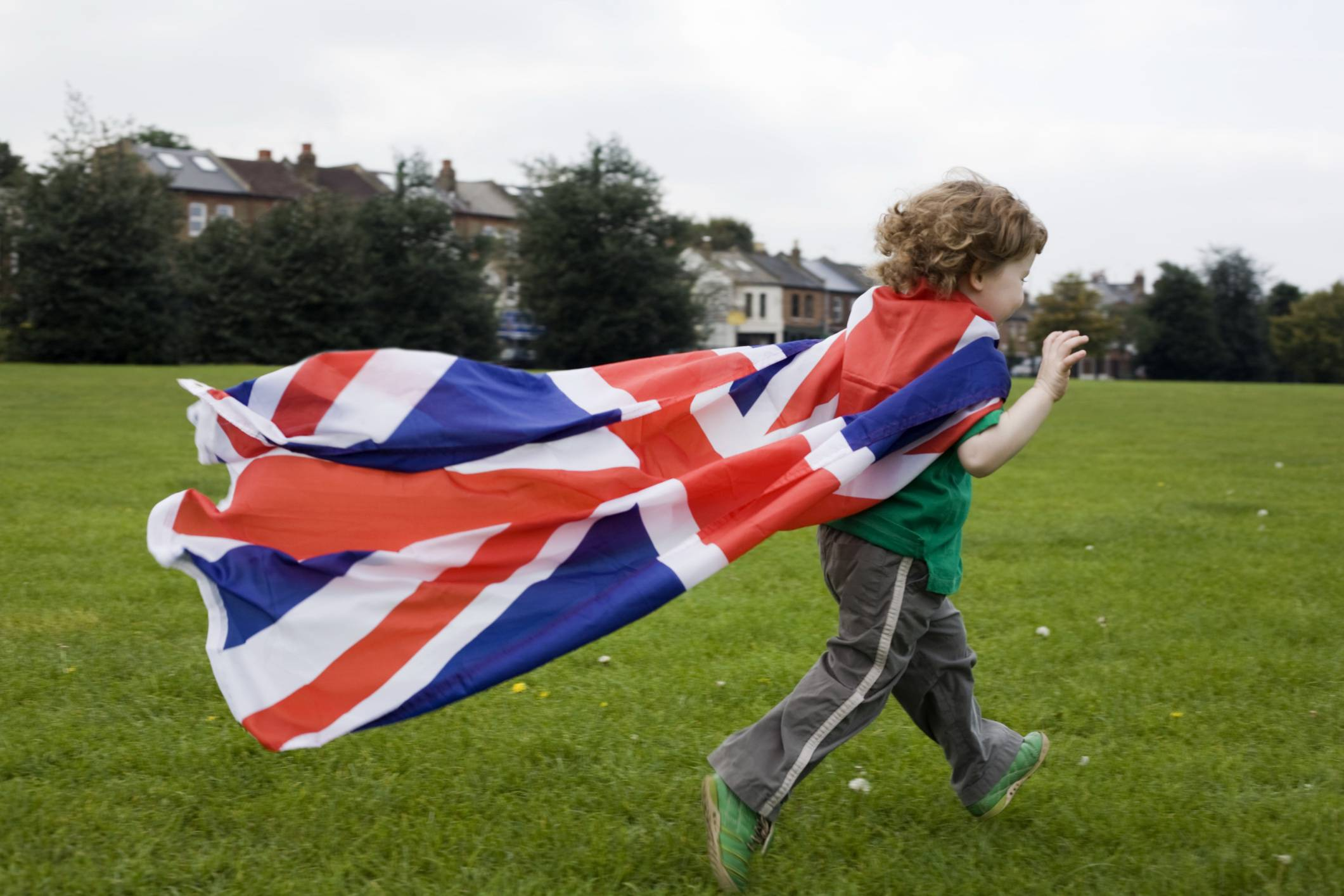 Ragazzo corre su prato con bandiera inglese come mantello