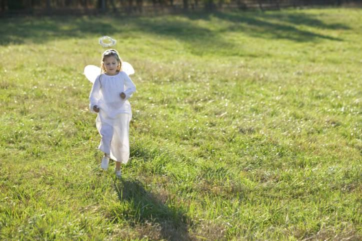 Bambina che corre vestita da angelo