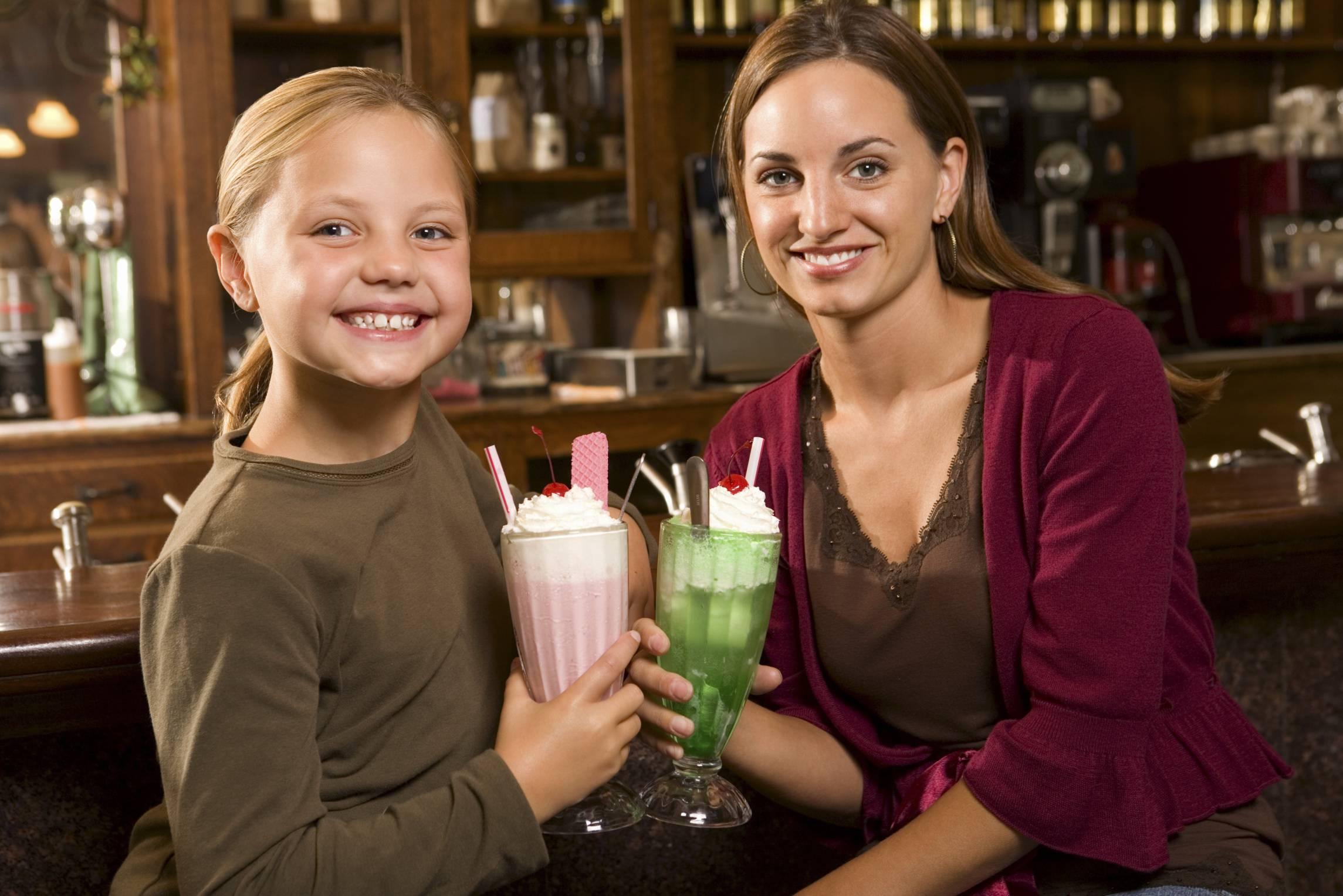 Mamma e figla bevono un frullato