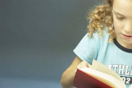 Bambina di 6 anni legge attentemente un libro rosso