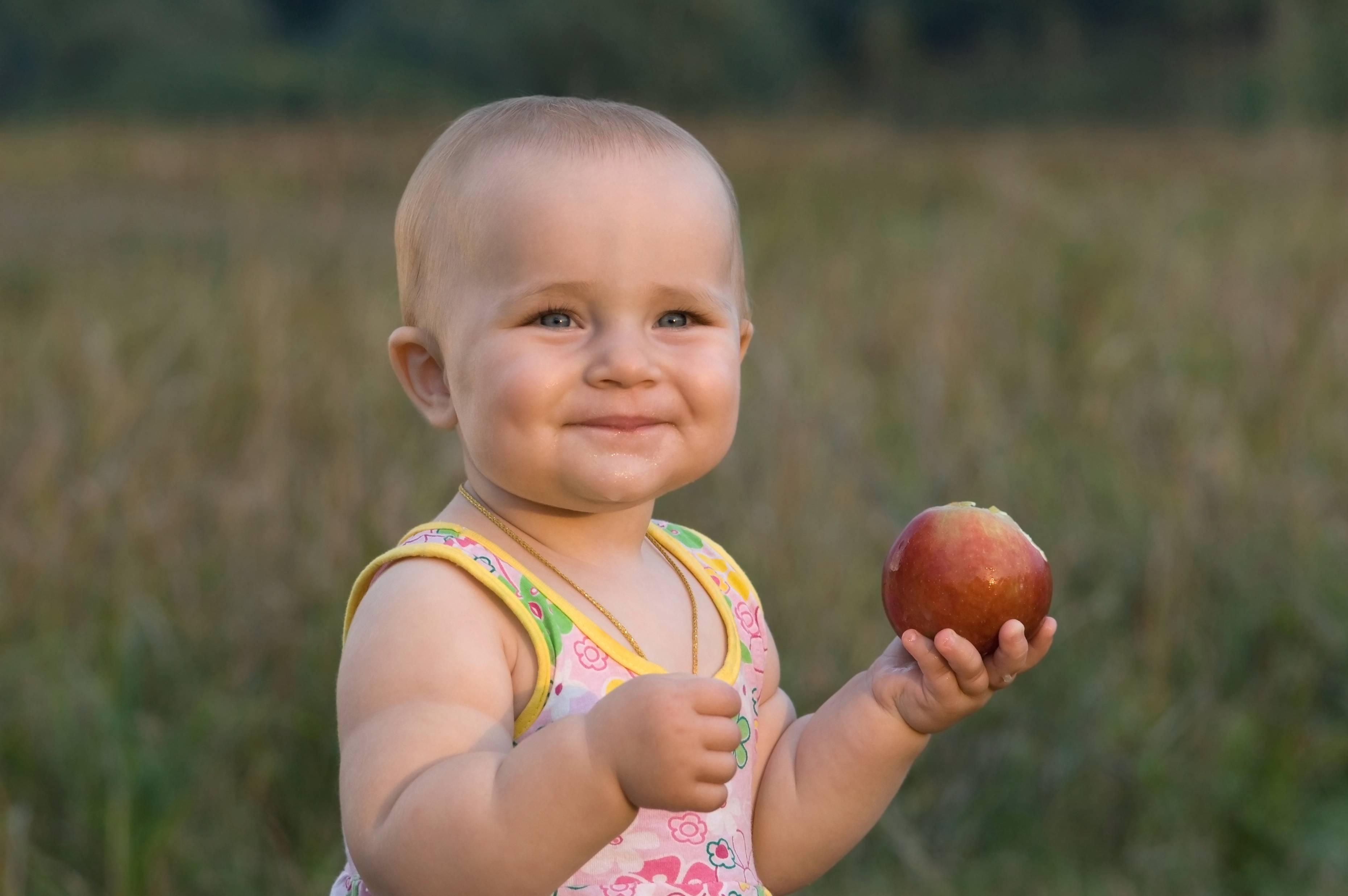 Bambina su un prato mostra i suoi primi denti con mela in mano