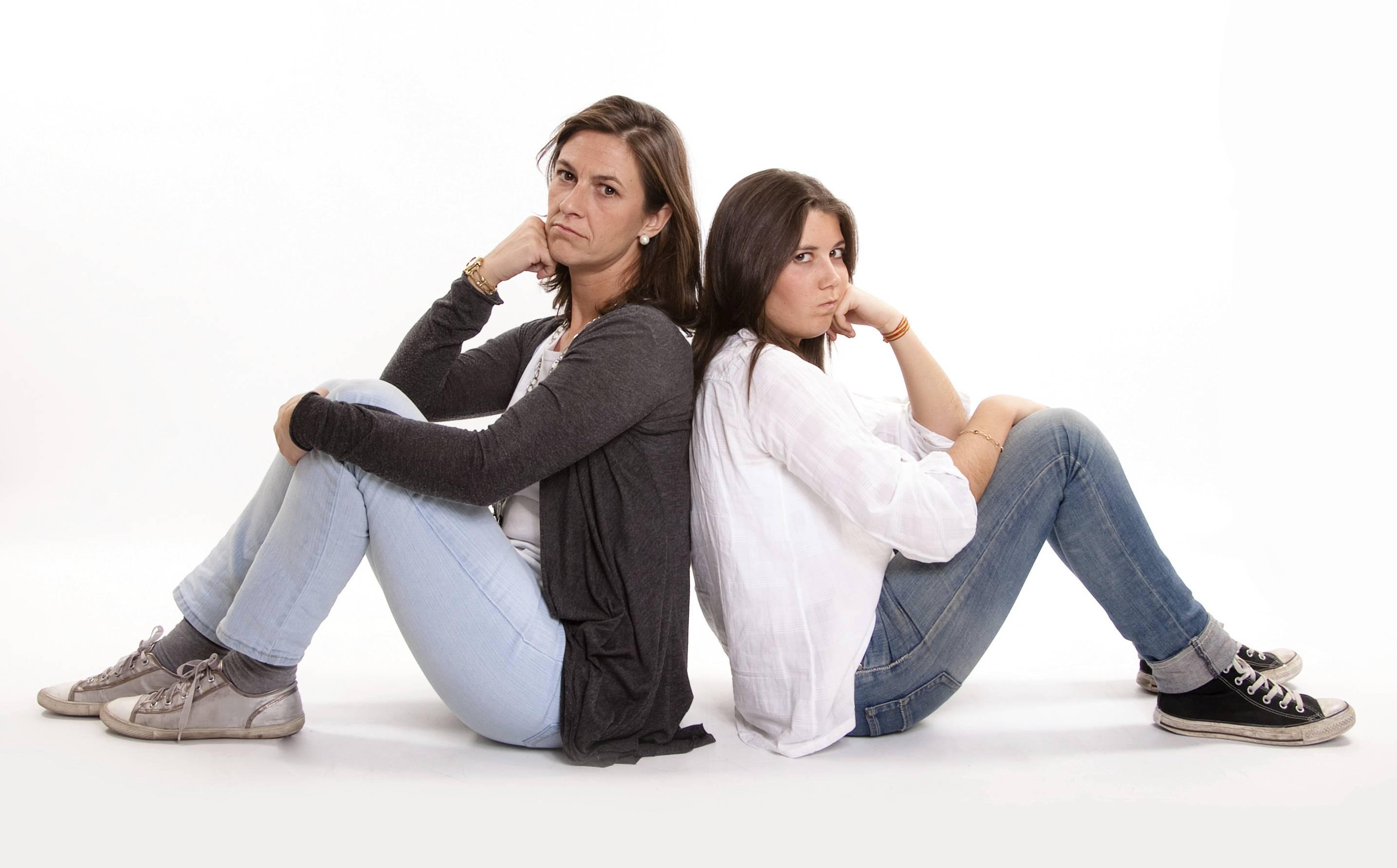 mamma e figlia adolescente sedute per terra si danno le spalle