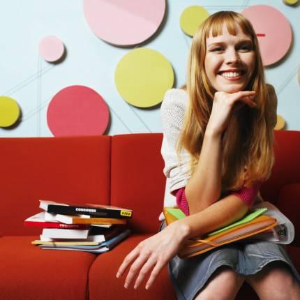 Ragazza sorridente seduta su divano rosso con libri intorno