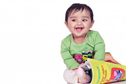 Bambina di 6-8 mesi sorridente con libro