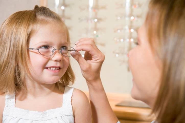 donna che prova gli occhiali a una bambina dall'oculista
