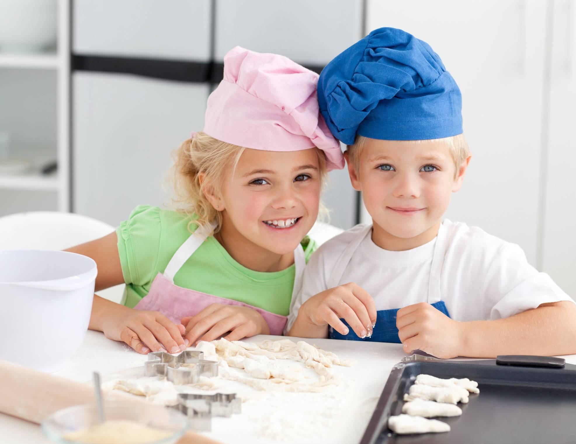 Due bambini giocano in cucina impastando