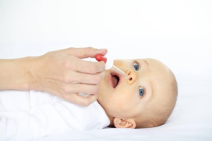 Bambino raffreddato, sdraiato per curarlo con gocce nasali