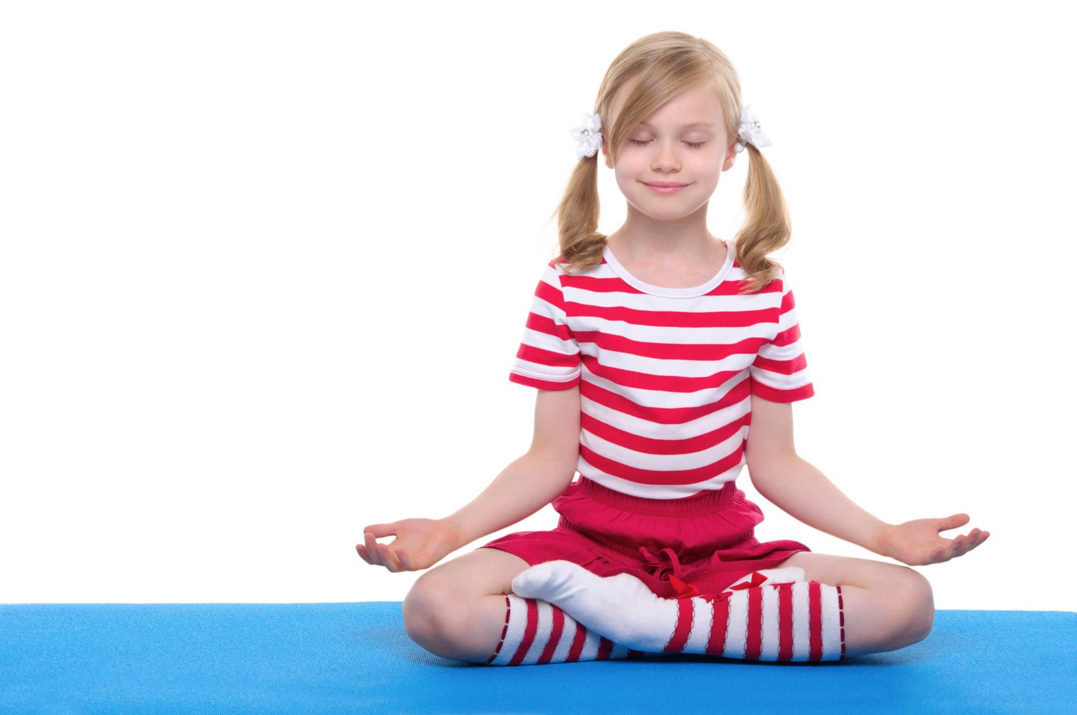 Bambina sorridente si rilassa in posizione yoga