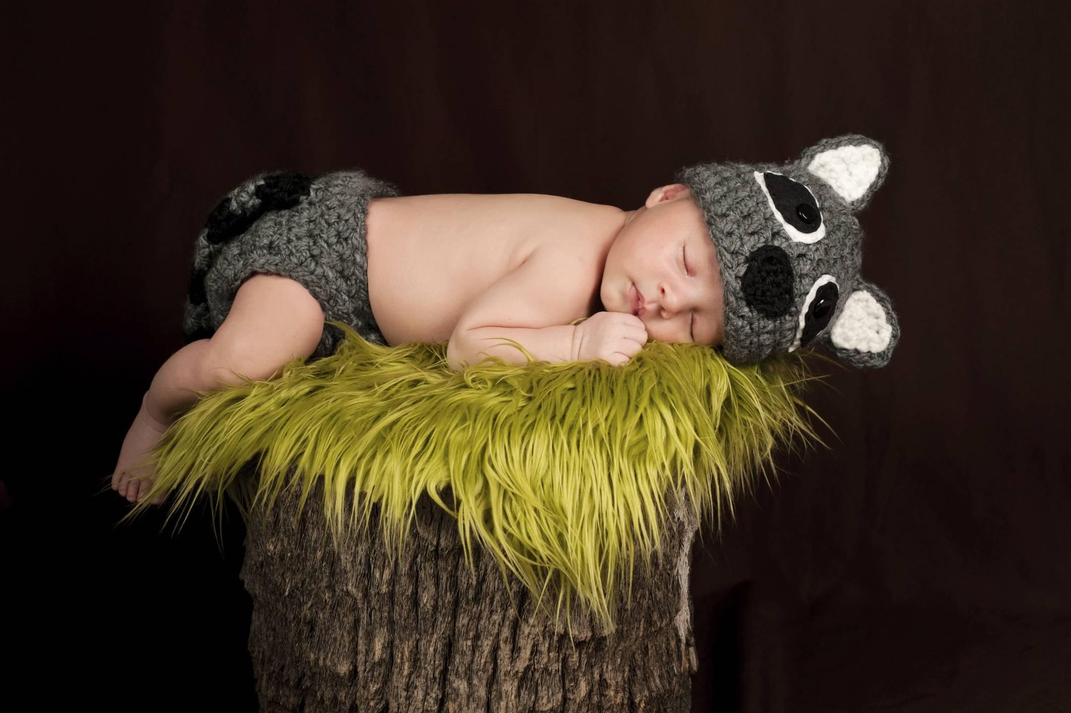 Neonato dorme su un tronco di albero