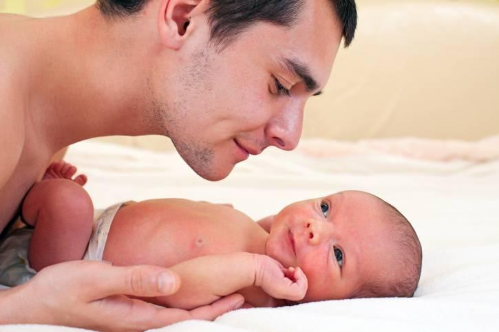 Giovane papà sorride a suo figlio