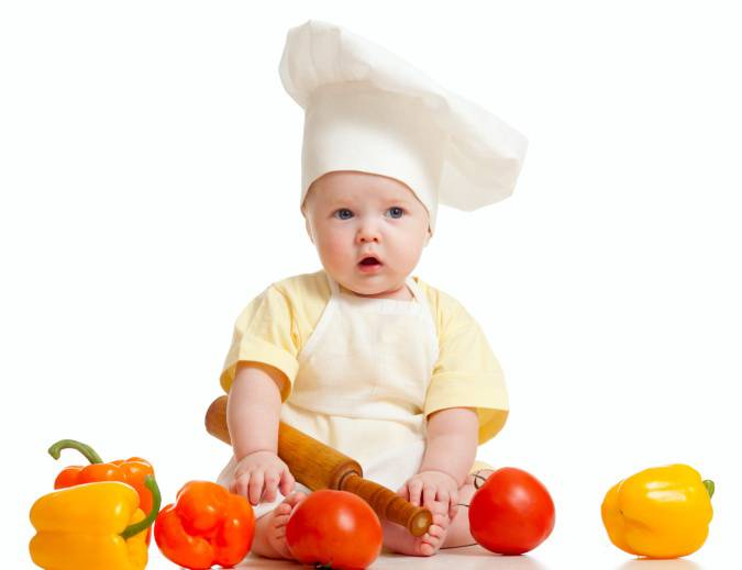 Bambino vestito da chef con verdura e frutta intorno
