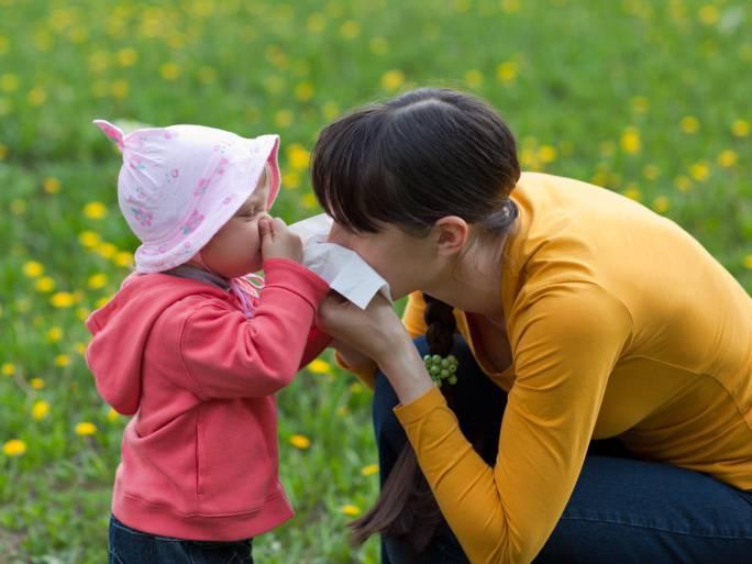 Bambina starnutisce vicina a sua mamma su un prato