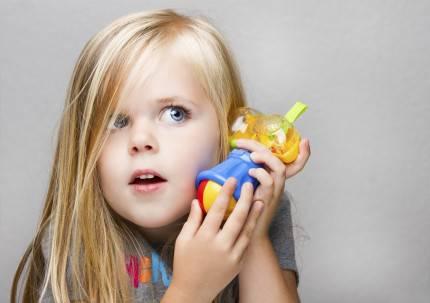 Bambina gioca facendo finta di parlare al telefono