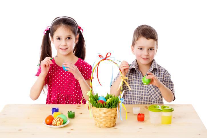 Due bambini che dipingono uova pasquali