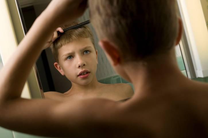 Ragazzo si pettina allo specchio