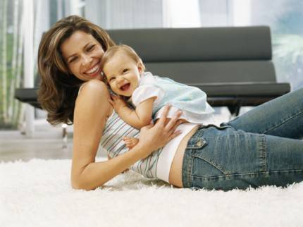 bambina sdraiata sulla mamma che ride