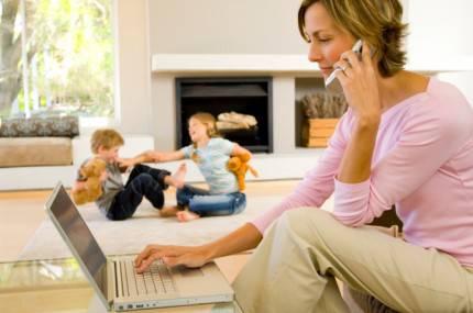 donna che parla al telefono,e usa il pc. sullo sfondo dei bambini che giocano