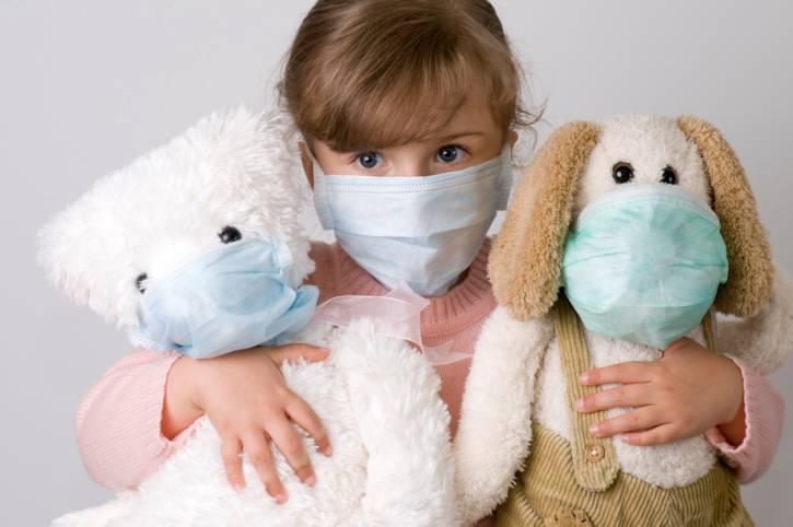 Bambina con maschera di protezione abbracciata a due pupazzi anche loro con maschera