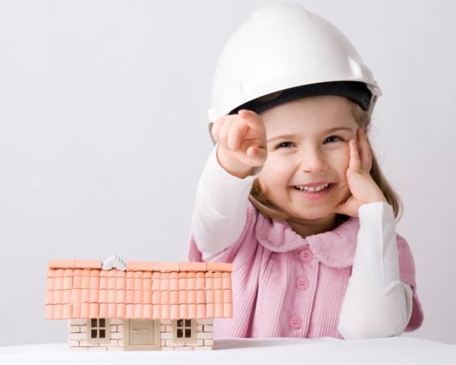 Bambina che indossa un caschetto di protezione di fronte a un modellino di casa
