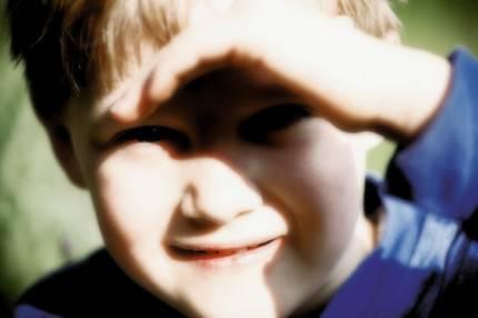 Bambino si ripara del sole con la mano