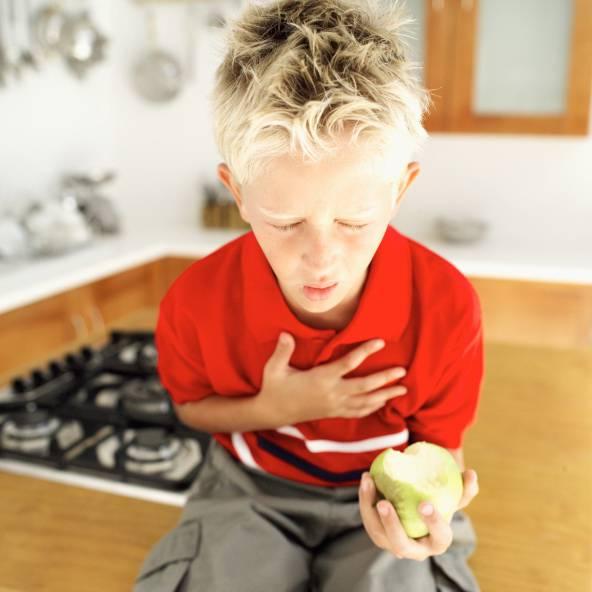 Ragazzo tossisce con mela in mano