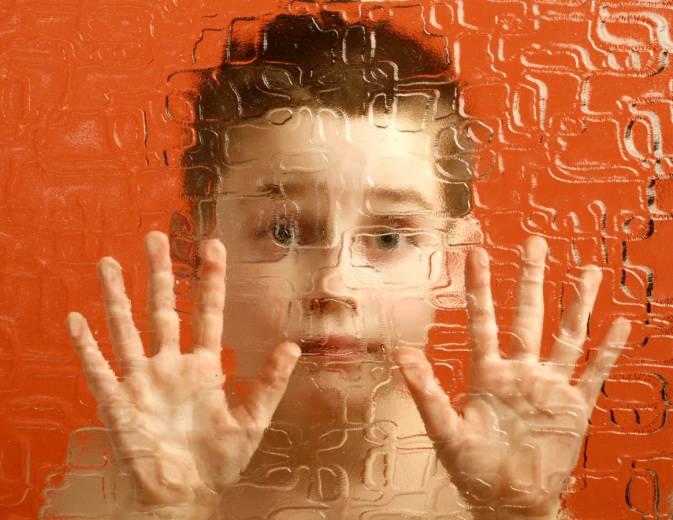 Bambino con occhi spalancati e mani poggiate su un vetro