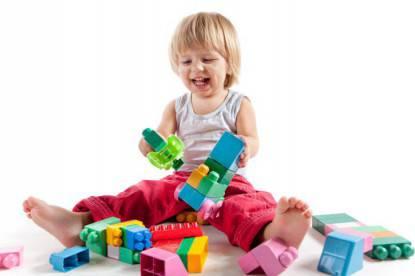 Bimbo sorridente gioca con giochi colorati