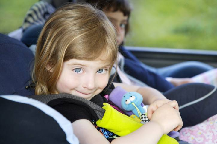 bambina sorridente sul seggiolino auto
