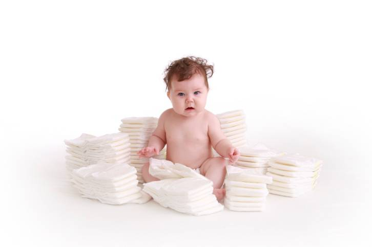 Bambino circondato da pannolini