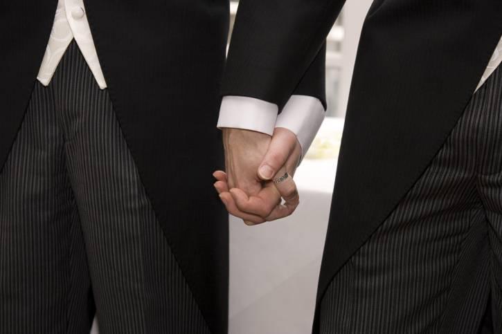 Due uomini si tengono per mano durante matrimonio
