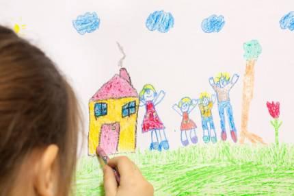 una bambina disegna la sua famiglia