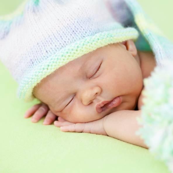 neonato riposa appoggiato sulle proprie mani