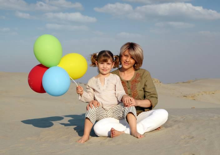 Madre e figlia in spiaggia con palloncini colorati