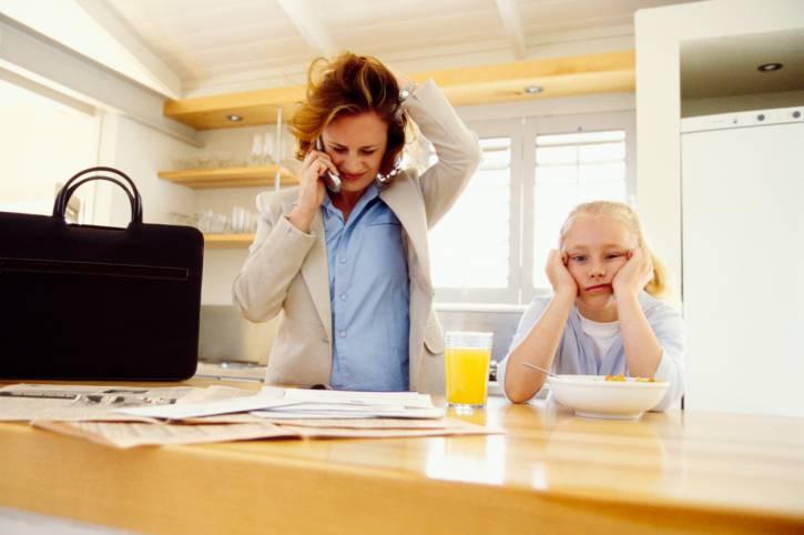 mamma stressata al telefono con bimbo accanto