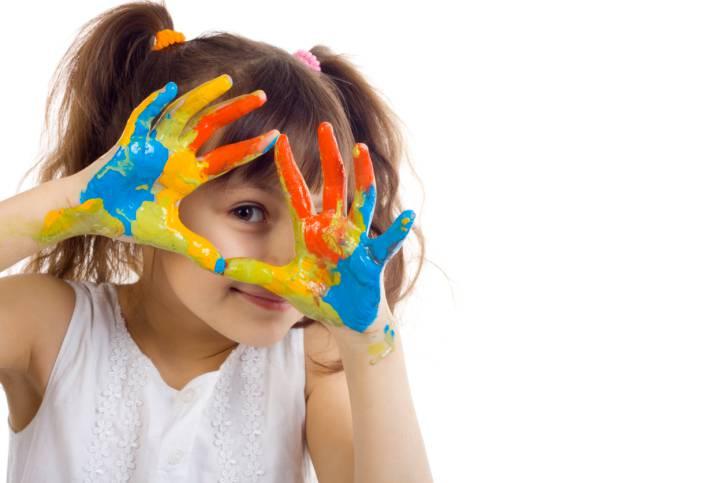 bambina sorridente con mani colorate