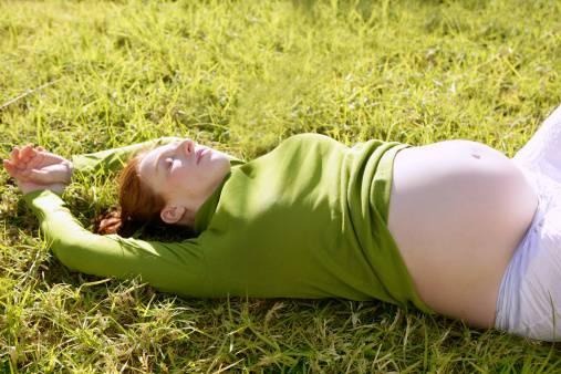 donna incinta sdraiata sull'erba
