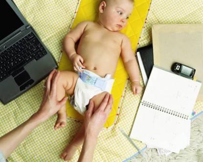 mamma cambia pannolino su scrivania di lavoro