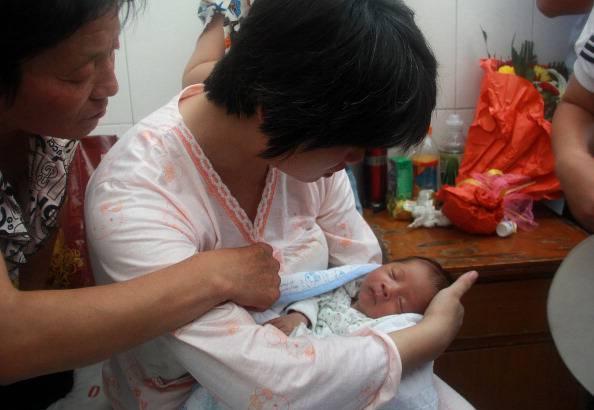 Mamma cinese con in braccio il figlio ritrovato